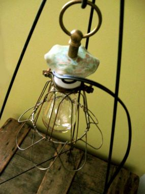 Industrial wire cage, porcelain socket, brass loop finial, rusty chain and an old copper washer.