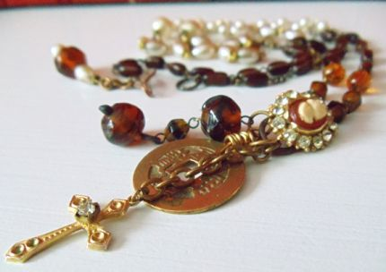 One of Nostalgic Summers new Converter Necklaces.These necklaces  are an assemblage of vintage beads, antique rosaries, medals, religious  icons and various antique jewelry pieces.The Converter Necklaces  all measure 20 to 22 long. They can be worn as the long pendant style  or wrapped for a shorter neckline.